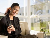Businesswoman sitting on chair and holding cell phone