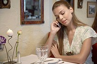 Woman talking on cell phone at dining table