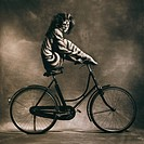 Studio shot of woman in cat dressed sitting on bicycle