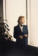 Business woman in office looking out of window
