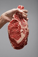 Woman´s hand holding raw steak close_up