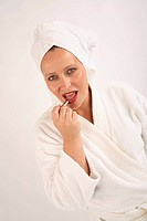 Woman applying lipstick, bathrobe