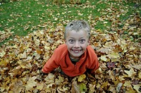 Nine-year-old boy in the autumn foliage