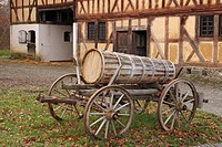 Ancient wooden carriage with wooden barrel in front of framework building, open-air museum Hessenpark, Hesse, Germany