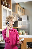 Woman Using Cell Phone While Holding Medicine Bottle
