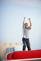 Boy Standing on Bed