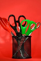 Scissors in different shapes and colours on red background