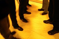 Legs of men wearing black in a yellow room