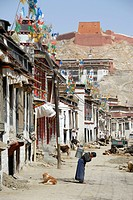 Street scene woman carries heavy bucket in old town Gyantse Tibet China