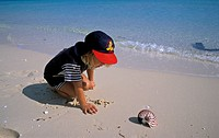 Child finding the shell of a nautilus, Ouvea, New Caledonia