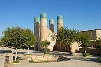 Four minarets Char Minar gatehouse behind trees Bukhara Uzbekistan