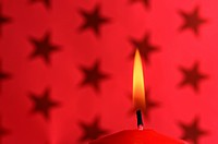 Lit candle in front of red christmas wrapping paper with stars