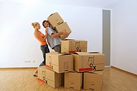 Young couple carrying cardboard boxes, moving