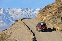 Jeep climbing dirt road with Sierra Mountain Range in background, California, USA