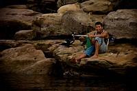 Seating youth in the Stone, Santo Elias Community, Negro River, Novo Airão, Amazonas, Brazil