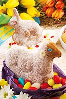 Easter bunny and lamb made of dough, sprinkled with icing sugar sitting on colourful eggs