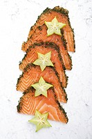 Sliced salmon gravlax garnished with starfruit
