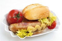 Bratwurst with mustard, bread roll and a tomato in a small bowl