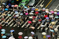 People with colorful umbrella in an intersection, Shanghai, China