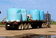 Agriculture _ Chemical tanks and herbicide concentrate loaded on a semi_truck / Canada _ Alberta, Taber