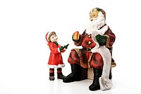 Santa Claus figurine handing small girl a Christmas present, Christmas decoration