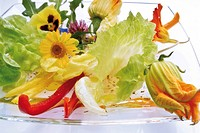 Salad of edible flowers including pansy, nasturtium, zucchini flower, yellow chamomile, borage blossoms, rucola, sliced peppers and vinaigrette dressi...