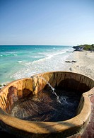 A hollowed out log jacuzzi on the terrace overlooking a beach coastline in Mexico