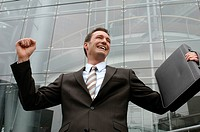 31-year-old businessman wearing a suit, standing in front of a glass facade