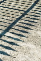 Shadow of wrought iron fence on gravel