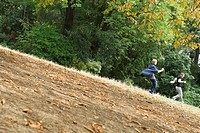 People running down hill in park