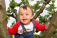Little girl, 13 months, on tree