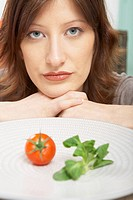 Young woman with a single tomato and piece of lettuce on her plate