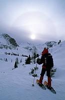 Woman wearing snowshoes and halo over Mount Scheibenkogel, Radstaedter Tauern Range, Salzburg, Austria, Europe