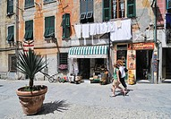Street scene, two young women walking past a house front with a small shop and laundry hanging on a washing line, Vernazzo, Liguria, Cinque Terre, Ita...