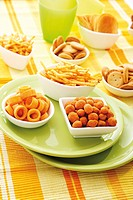 Various spiced snacks in bowls, crisps, peanut flips, potato sticks, roasted peanuts and potato rings