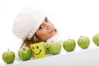 Young woman wearing a scarf and a cap, behind a row of green apples and a smiley mug