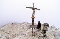 Female hiker next to the cross on the peak of Mount Kleiner Lagazuoi, 2778 m, Cortina d'Ampezzo, Ampezzo Dolomites, Italy, Europe