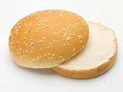 A hamburger bun with sesame seeds, split