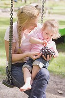 Mother and young daughter eating grapes on a swing