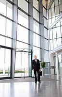 A mature businessman standing in the lobby of a modern office building
