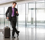 A businessman waiting in an office lobby or airport concourse with a suitcase