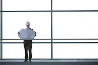An architect or developer standing on walkway of office building, looking at plans