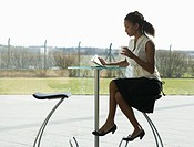 A businesswoman sitting at a table, drinking coffee and reading a magazine