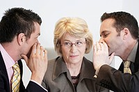 mature businesswomen listening to two male colleagues whispering