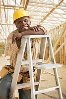 African construction worker in hard_hat sitting on ladder