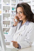 Hispanic pharmacist talking on telephone