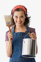 Hispanic woman holding paint brush and paint can