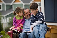 Father reading to son and daughter on porch