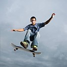 Mixed race teenager in mid_air on skateboard