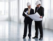 Two architects wearing hard hats looking at plans